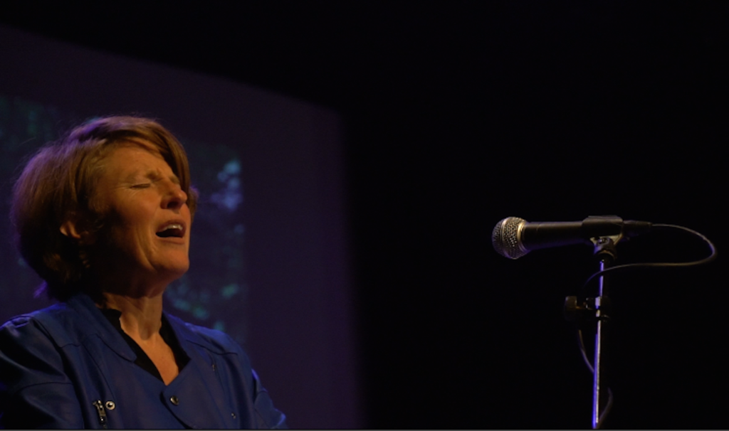 Lisa Fingleton with eyes closed sings into a mic against a dark background