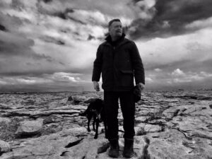 Black and white picture of Dermott Petty and his black dog in the Burren on the limestone rocks