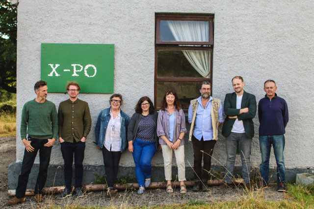 Group of eight people leaning against the grey wall of the X-PO
