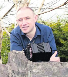 Tim Collins leaning on a stone wall holding a concertina