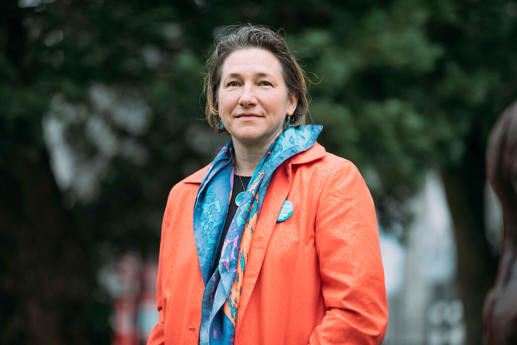 Sara Foust wearing a bright orange coat and blue scarf against a background of dark blurry trees