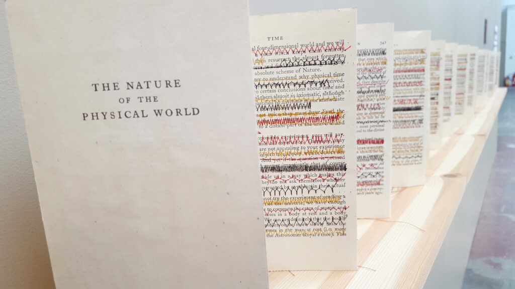 Hand Made Book with colour stitching over the text displayed concertina like along a pale wooden shelf
