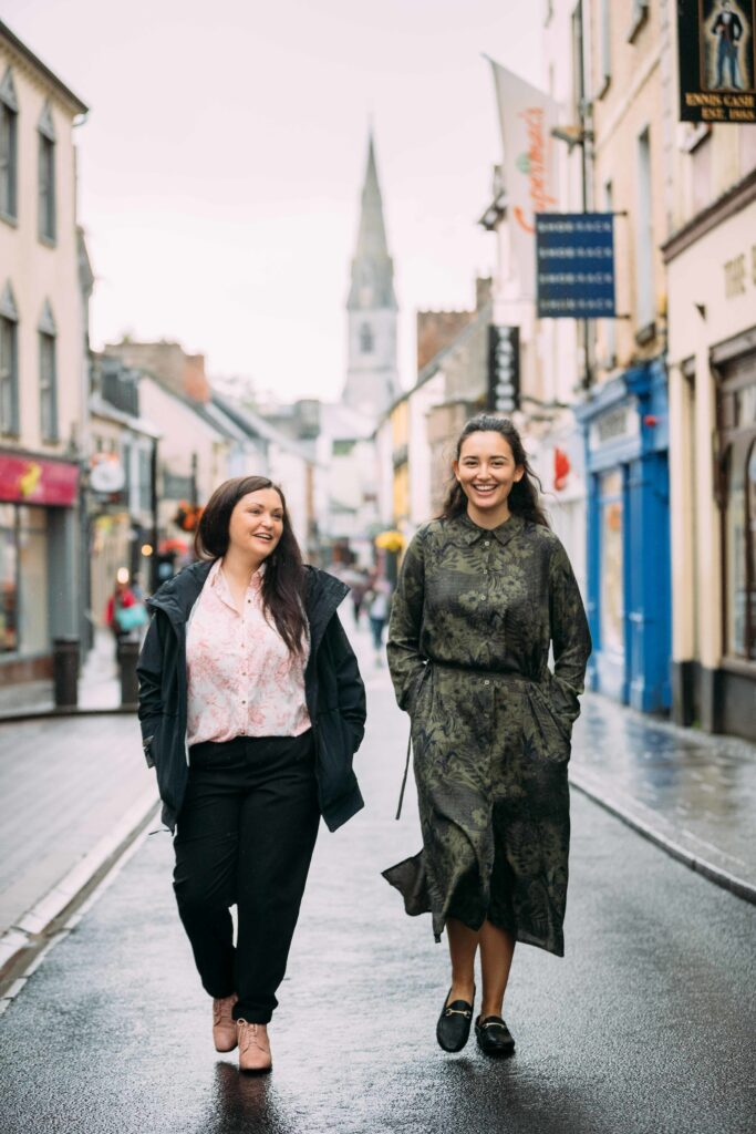 Two women at the top of O'Connell Street Ennis with the street off focus in the background