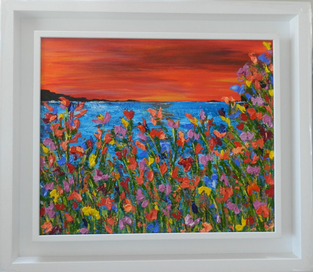 Image of colourful flowers against the blue sea with a red sunset sky