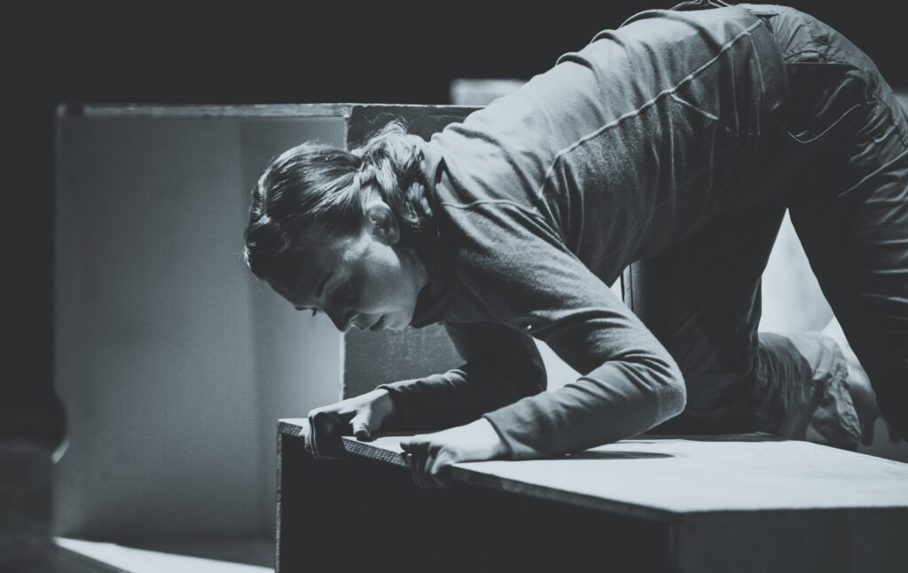 Black and white image of Maria Svensson on all fours on a box peering over the edge