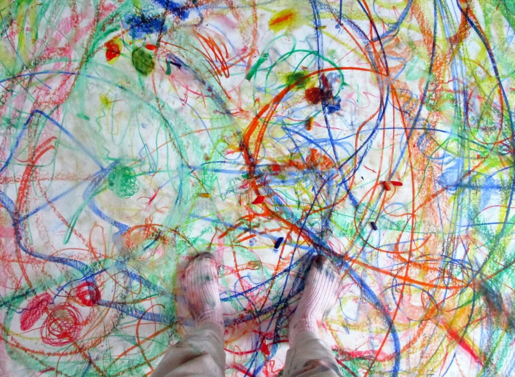 Feet in white socks standing on a white sheet covered with colourful crayon scribbles