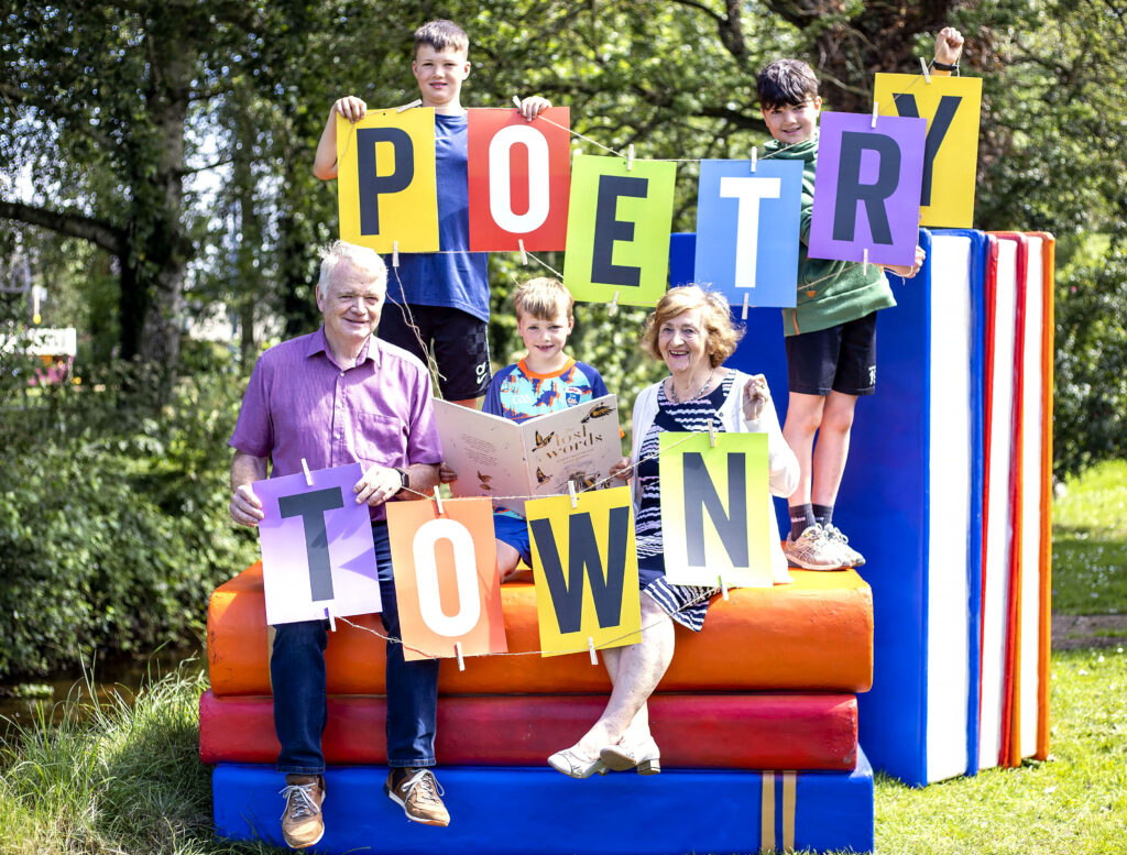 Family hold up letters that read Poetry Town
