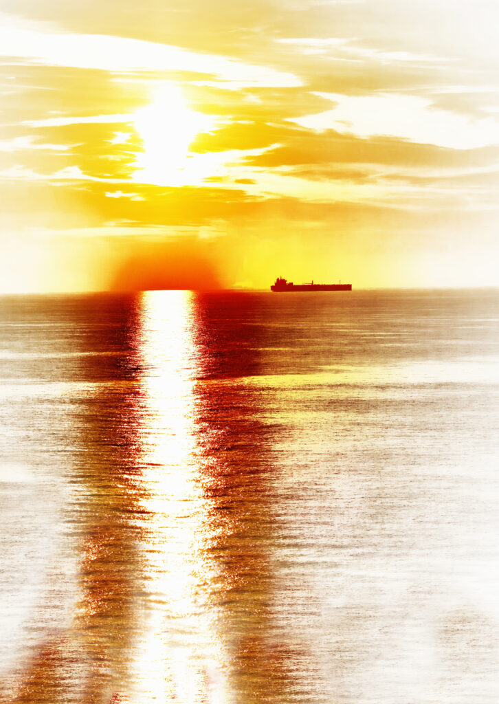 Large trawler approaching a red setting sun casting yellow in the sky and a shining path through a red sea scene