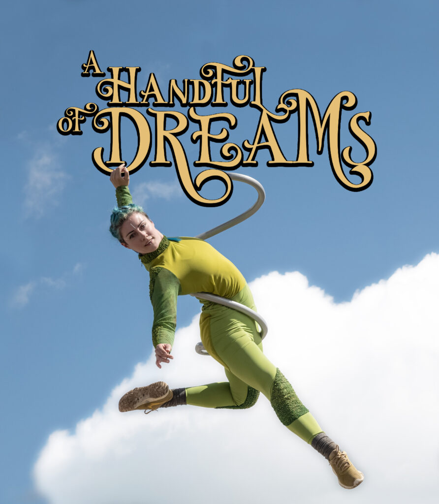An Aerial Dancer in green hanging from the Text A Handful Of Dreams against a blue sky background with white clouds