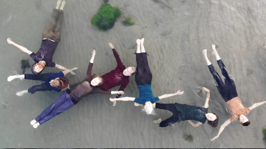 7 people floating on their backs in shallow water, sandy underneath