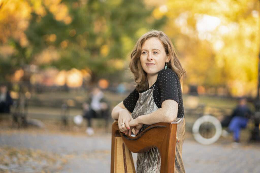 Niamh O Brien, leaning on her harp, with autumnal sunshine shing through the trees behind her