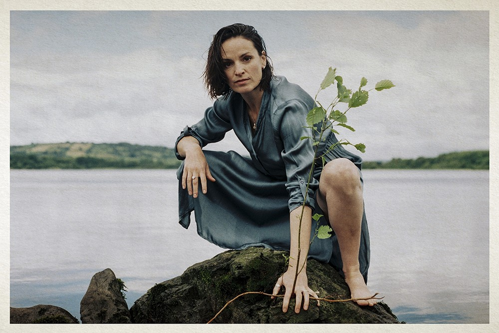 Woman bending down on a rock in a lake holding a branch
